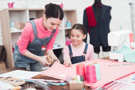 女性が生地から衣類を切り取る。彼女の隣には小さな女の子がいます。彼らは縫製ワークショップでお母さんと一緒です。 写真素材