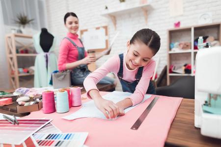 Kleines Mädchen zeichnet eine Kreide auf das Tuch. Sie sind mit der Mutter in der Nähwerkstatt. Sie sind gut gelaunt.