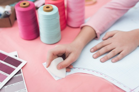 Little girl draws a chalk on the cloth. They are with mother in the sewing workshop. They are in a good mood. Stock Photo