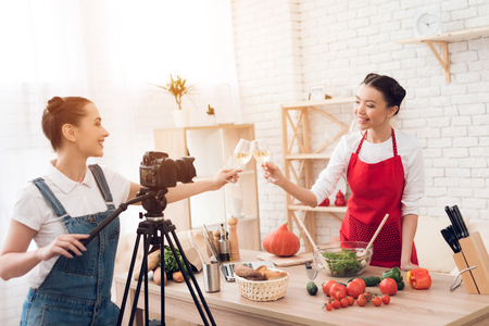 Two culinary bloggers in red aprons tasting winewith one girl behind camera.