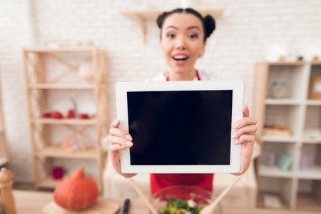 Culinary blogger girl in red apron holds up blank tablet to camera.
