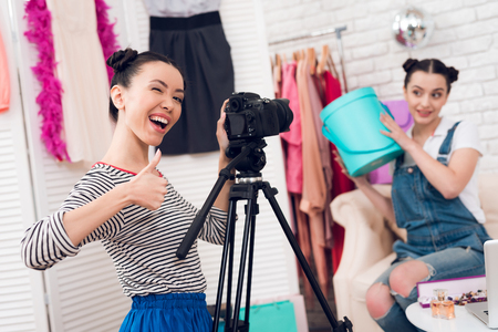 Two fashion blogger girls in jeans and shirt with skirt hold up colorful bag with one girl behind camera. Stock Photo