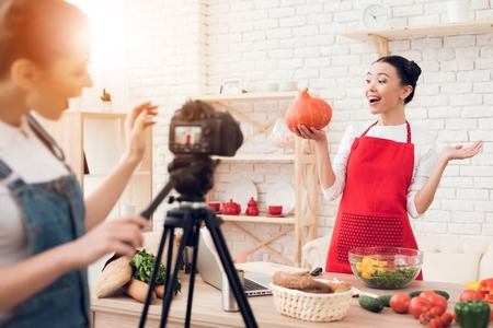 Two culinary bloggers in red aprons hold up pumpkin with one girl behind camera.