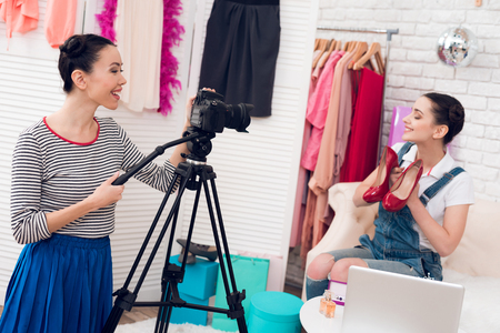 Two fashion blogger girls in jeans and shirt with skirt hold up red shoes with one girl behind camera.