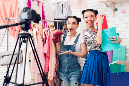 Two fashion blogger girls in jeans and shirt with skirt present colorful bags and red shoes to camera. Imagens