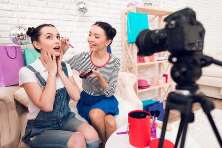 Two fashion blogger girls in jeans and shirt with skirt hold up brushes and eye shadows to camera.