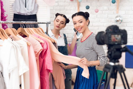 Two fashion blogger girls in jeans and shirt with skirt present colorful dress to camera. Zdjęcie Seryjne