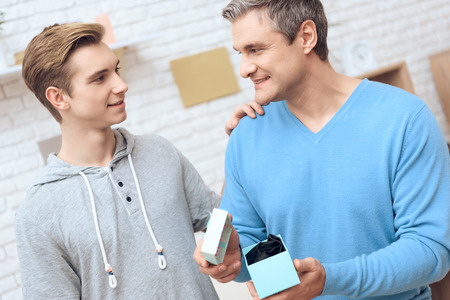 Father is drinking coffee, son is surprising him with a present. Father and son are bonding. Stock Photo