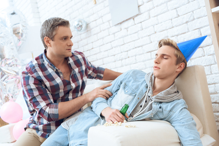After birthday party troubled teenager is hangover. Father is trying to talk to him, but son is too sick to listen. Stock Photo