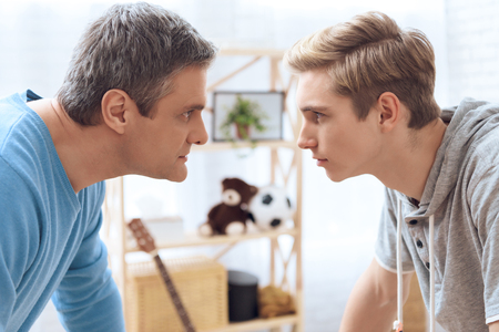 Father and son standing face to face. Father and troubled teenager trying to intimidate each other looking eye to eye. Stock Photo