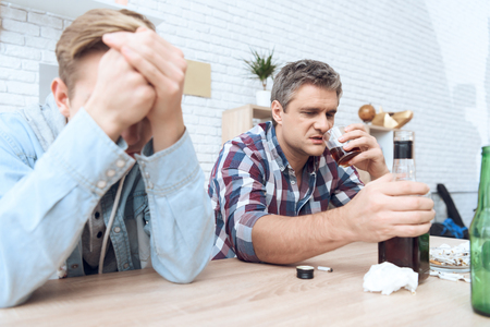 Drunk father is sitting at table with glass and bottles, drinking. His son is helpless to stop him. Stock Photo
