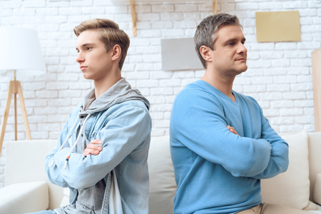 Father and son are refusing to talk to each other, sitting back to back away from each other. Banque d'images - 97679336