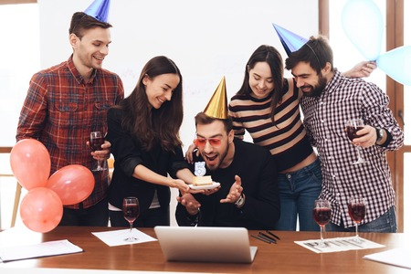 A group of office employees celebrate the fifth anniversary of their company. They are dressed in holiday caps. They are smiling.