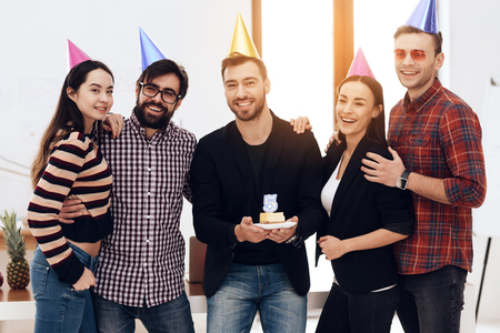 Young employees of the company celebrate a corporate holiday. They put on holiday caps and have fun.