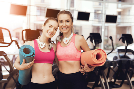 Mother and daughter in sportswear with mats standing at the gym. They look happy, fashionable and fit.