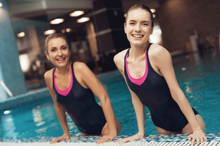 Mother and daughter in swimsuits at border of pool at the gym. They look happy, fashionable and fit. Stock Photo - 97626527