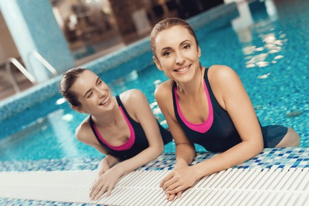 Two women in swimsuits at the border of pool at the gym. They look happy, fashionable and fit. Banco de Imagens