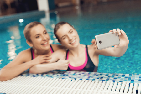 Mother and daughter in swimsuits at border of pool taking selfie at the gym. They look happy, fashionable and fit.
