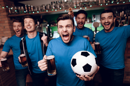 Five soccer fans drinking beer celebrating and cheering at sports bar. They are supporting blue team.