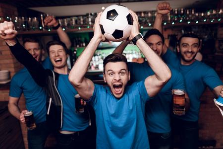 스포츠 바에서 맥주를 축하하고 환호하는 다섯 축구 팬. 그들은 블루 팀을 지원하고 있습니다.
