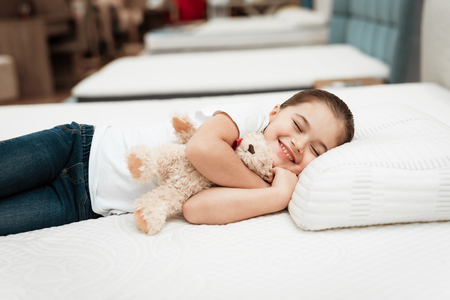 Smiling little girl lies on n orthopedic mattress in a furniture store. Smiling little girl hugs teddy bear on mattress in furniture store. Archivio Fotografico - 97679876