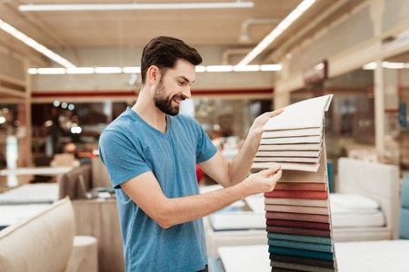 Handsome bearded man chooses color on color palette. Selecting color of mattress on color palette guide. Selection of color of cloth in color catalog.