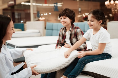 Beautiful woman dressed in white robe shows orthopedic pillow to young children sitting on mattress. Choosing pillow in store.