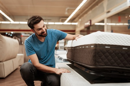 Young bearded man is testing mattress in furniture store. Orthopedic mattress for a healthy posture. Checking mattress in furniture store. Stock Photo
