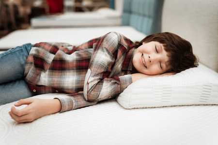 Joyful boy enjoying softness of orthopedic pillow rejoices in furniture store. Joyful little boy lies on orthopedic pillow in mattress store. Stok Fotoğraf