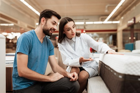 Lovely woman consultant demonstrates orthopedic mattress to confident man in furniture store. Purchase of orthopedic mattress. Choosing mattress in store.