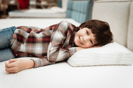 Joyful boy enjoying softness of orthopedic pillow rejoices in furniture store. Joyful little boy lies on orthopedic pillow in mattress store. Stok Fotoğraf