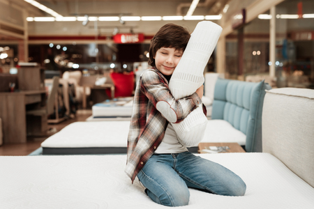 Joyful boy enjoying softness of orthopedic pillow rejoices in furniture store. Joyful little boy hugs orthopedic pillow sitting on mattress. 스톡 콘텐츠