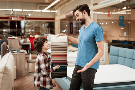 Bearded man with young boy chooses color on color palette. Selecting color of mattress on color palette guide. Selection of color of cloth in color catalog.