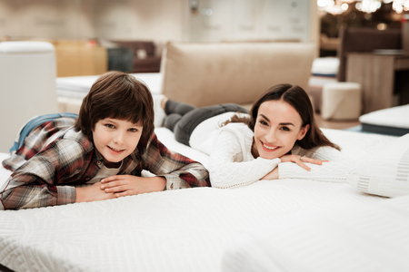 Young beautiful woman with cute little boy lies on bed in mattress store. Family checking softness of mattress. Purchase of orthopedic mattress.