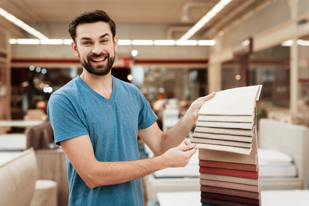 Satisfied bearded man choose color on color palette. Selecting color of mattress on color palette guide. Selection of color of cloth in color catalog.