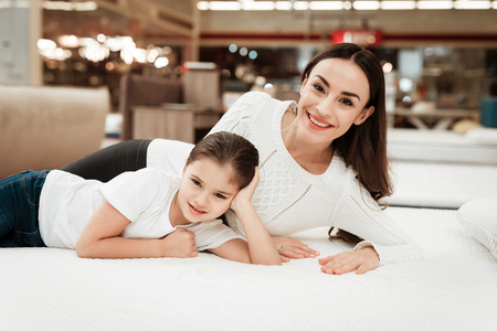 Young beautiful woman with cute little girl lies on bed in mattress store. Family checking softness of mattress. Purchase of orthopedic mattress.