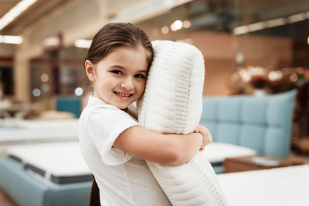 Nice little girl hugs pillow in store of orthopedic mattresses. Testing softness of pillow. Check softness of orthopedic pillow. Stok Fotoğraf