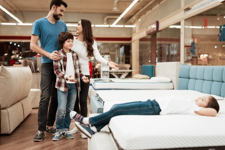 Blissful family buys new orthopedic mattress in furniture store. Happy family choosing mattresses in store. Orthopedic mattress, for comfortable sleep and healthy posture. Imagens