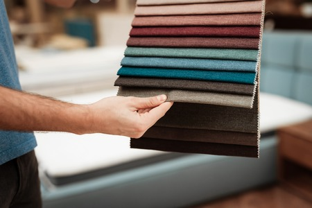 Mans arm chooses color on color palette. Selecting color of mattress on color palette guide. Selection of color of cloth in color catalog.