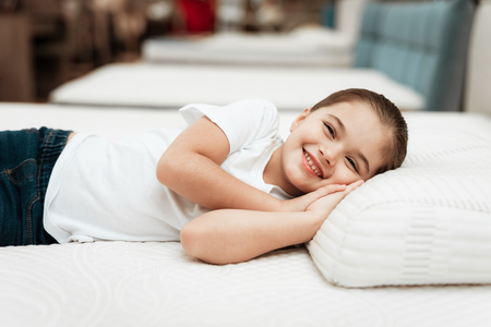 Smiling little girl lies on n orthopedic mattress in a furniture store. Testing mattress. Concept of healthy posture.
