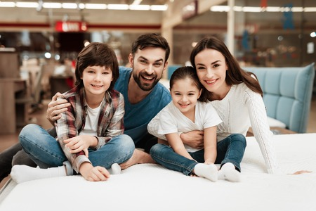 Big happy family chooses soft mattresses in orthopedic furniture store. Healthy posture concept. Orthopedic mattresses, for comfortable sleep and healthy posture.