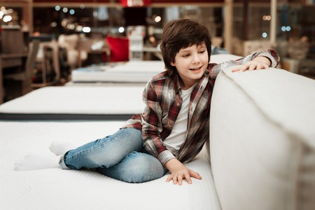 Joyful boy in store sits on bed in orthopedic mattress store. Check for softness of orthopedic furniture. Choosing mattress in store. 스톡 콘텐츠
