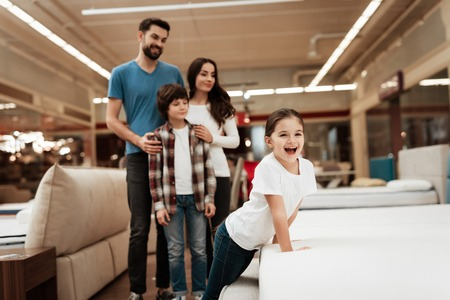 Happy family buys new orthopedic mattress in furniture store. Blissful choosing choosing mattresses in store. Orthopedic mattress, for comfortable sleep and healthy posture. Foto de archivo - 97679938