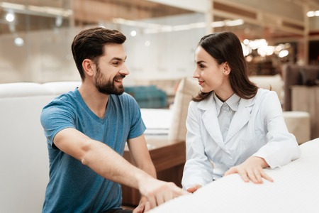 Confident man with beard communicates with beautiful girl consultant in mattress store. Orthopedic mattress, for comfortable sleep and healthy posture. Фото со стока