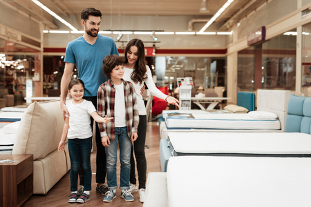 Happy family buys new orthopedic mattress in furniture store. Blissful choosing choosing mattresses in store. Orthopedic mattress, for comfortable sleep and healthy posture. Foto de archivo - 97645350