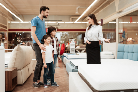 Young girl consultant demonstrates orthopedic mattress to young father with children in furniture store. Purchase of orthopedic mattress. Sale of orthopedic mattress in furniture store.