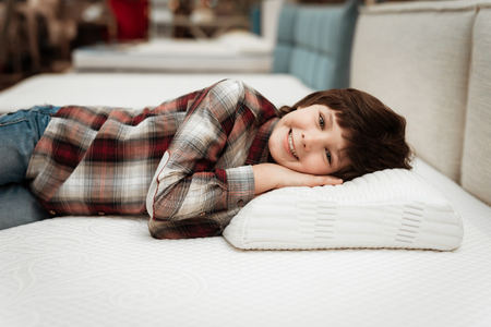 Joyful little boy lies on orthopedic pillow in mattress store. Check for softness of orthopedic. Choosing mattress in store.