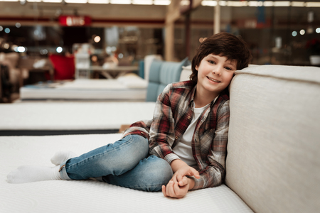 Joyful boy in store sits on bed in orthopedic mattress store. Check for softness of orthopedic furniture. Choosing mattress in store. Stok Fotoğraf