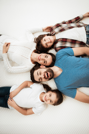 Adult happy couple with cute little son and daughter lies on bed in mattress store. Testing softness of mattress. Check softness of mattress. Stock Photo