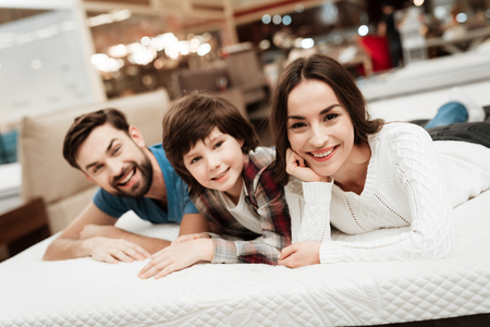 Lovely bearded man, together with his beautiful wife and son, relaxes on the mattress in the store. Check softness of mattress 版權商用圖片 - 97679981